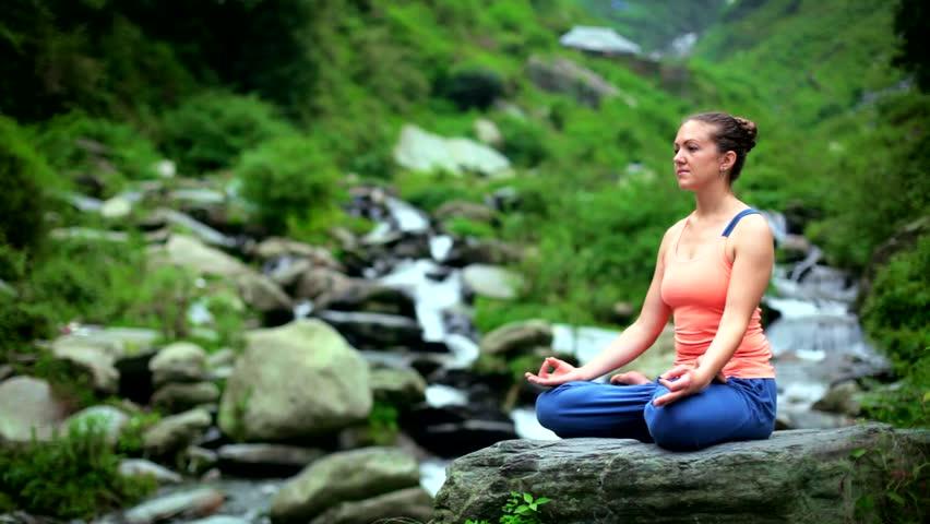 Young sporty fit woman doing yoga - meditating in Padmasana (Lotus Pose) outdoors at tropical waterfall. Himachal Pradesh, India | Shutterstock HD Video #1012469852
