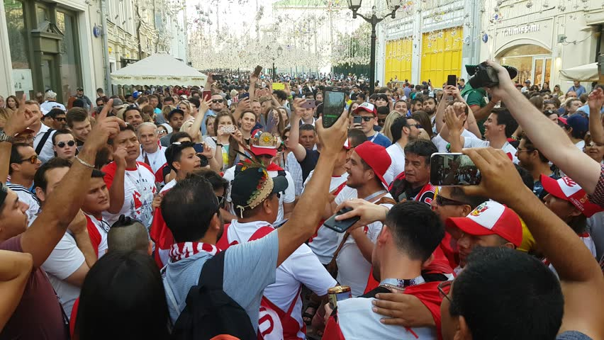 JUN 16, 2018, MOSCOW, RUSSIA: Peruvian fans having fan on the street. People in national soccer team wear posing and dancing for photographer in Moscow