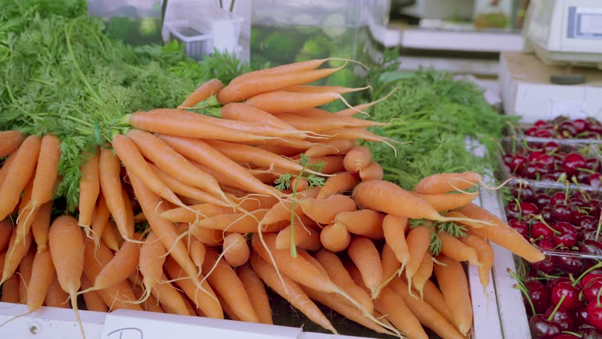 Freshly picked carrots on the tables in the stall to be sold to the customers on the market | Shutterstock HD Video #1012496642