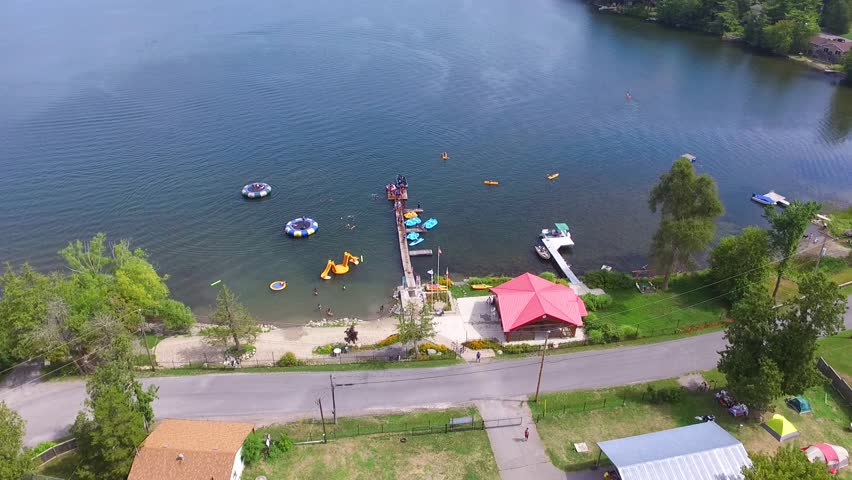 aerial shot of a campground with tents and trailers near a blue lake in the summer