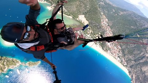 Paragliding oludeniz flying turkey Friday, June 15 - 2018 / Paragliding in the sky. Paraglider tandem flying over the sea with blue water, beach and mountains in sunrise. Aerial view of paraglider.