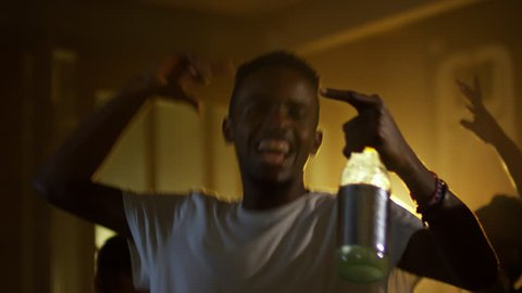Medium shot of overjoyed black man jumping with bottle of alcohol and enjoying music at party with friends