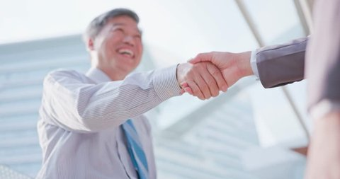 old business man shake hands with his partner