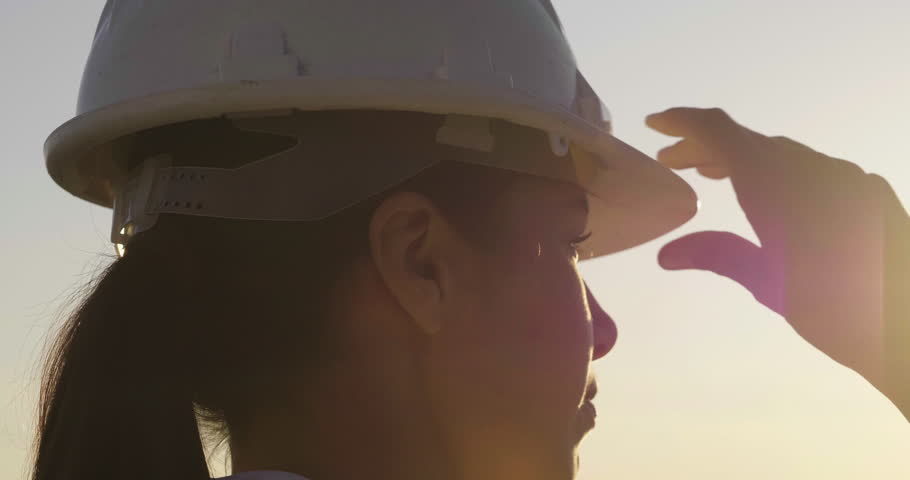 Slow motion close up of a woman engineer looking at the horizon proud of her work and putting a construction helmet on at sunset.Concept of: career, success, work and engineering.