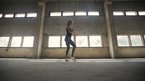 Bendy young gymnast doing the splits, wearing black vest, gray leggings and white sneakers, indoor shot in giant empty room before windows