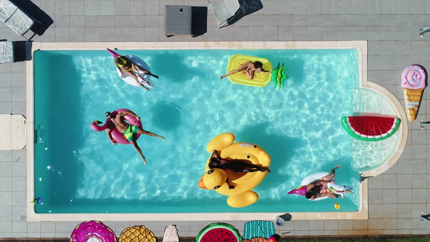 Group of friends having fun in the swimming pool with inflatable colored toys | Shutterstock HD Video #1012507052