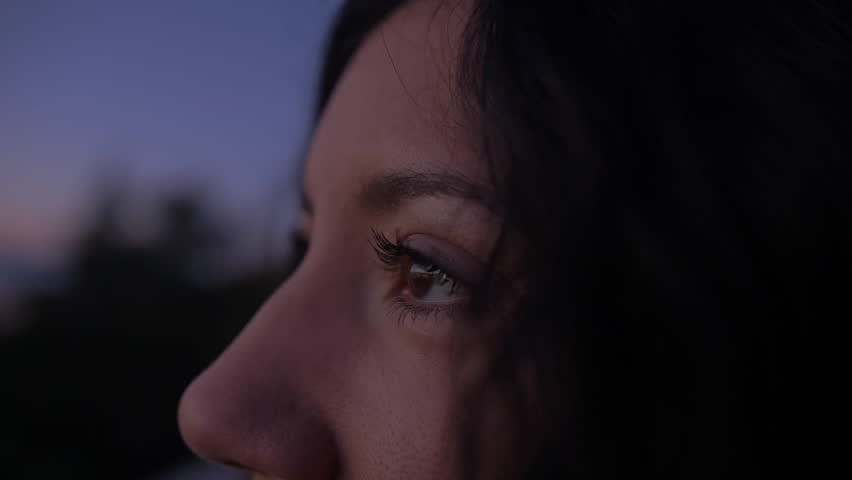 Close of Woman's Face and Eyes During Dark Sunrise/Sunset as She Admires the Colorful Blue and Purple Tones in the Sky