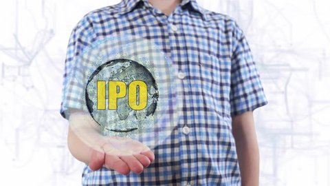 Young man shows a hologram of the planet Earth and text IPO. Boy with future technology 3d projection on a modern white digital background