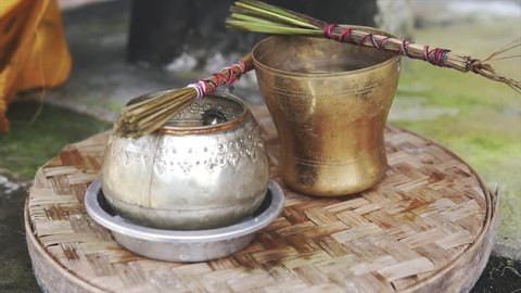 Bali, Indonesia Fabruary 3, 2018: Holy tools for Balinese priest for performing ritual, on ceremony, metal jar and brush for splashing the water