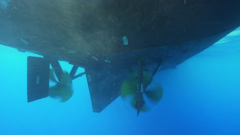 Underwater shot of big boat propeller spinning as they move across the ocean.