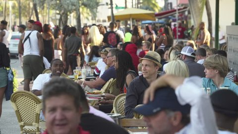 Miami beach cityscape, street view. Crowd of students and tourists in a restaurant on the Ocean drive, South Beach - April 2018: Miami beach, Florida, US