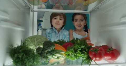 little turkish brother and sister searching in fridge and choosing from vegetables 4k