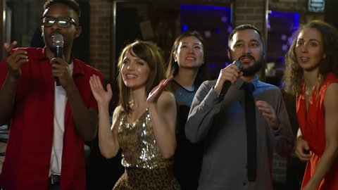 Medium shot of five young people of different ethnicities dancing and  singing to rhythmic music when partying in karaoke bar
