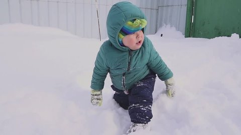One year old boy plays in the snow yard