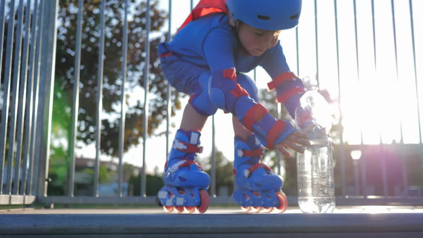 drinking water, Rollerblading child in helmet with plastic bottle into hand outdoors in backlight