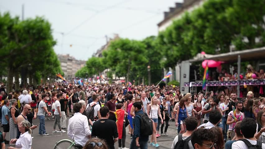 STRASBOURG, FRANCE - JUN 10, 2017: Crowd near Gay truck in city center at gay LGBT pride - tilt-shift lens with thousands of people dancing on the street - elevated view