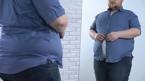 Plump man buttoning up tight shirt, oversize clothing problem, appearance