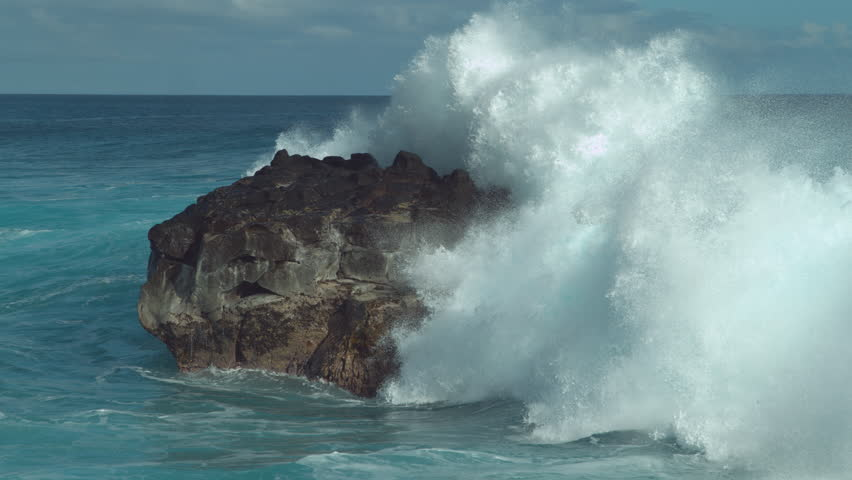 SLOW MOTION: Powerful ocean wave splashes across a big rock in the middle of the rough exotic sea. Breathtaking view of violent breaking wave foaming over a black rock near rocky tropical shore.