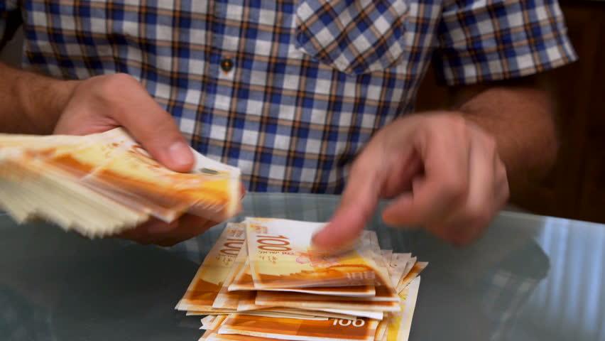 Counting New Israeli Shekels, bundle of money