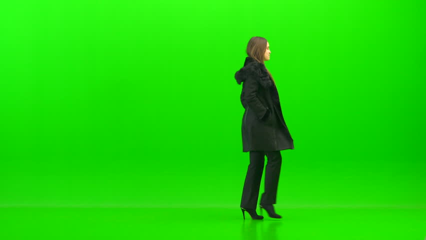 woman walking with a coat on the green background