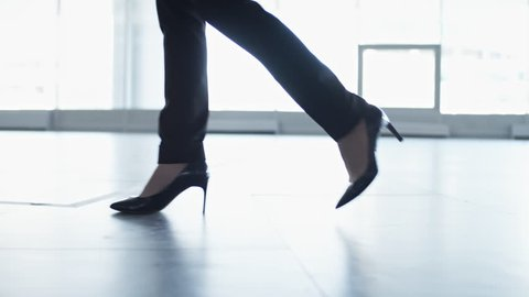 Side view closeup shot of legs of businesswoman in elegant high heel shoes and black trousers walking through hallway of office building