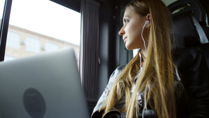 Medium shot of relaxed young woman looking out of window and listening to music when working on laptop computer in car | Shutterstock HD Video #1012645682