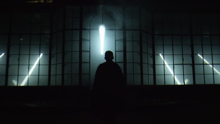 Man walking towards a monumental structure in the darkness | Shutterstock HD Video #1012646612