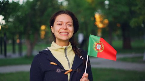 Slow motion portrait of pretty Portugese woman holding official flag of Portugal, smiling and looking at camera. Active women, sports fans, countries and people concept.