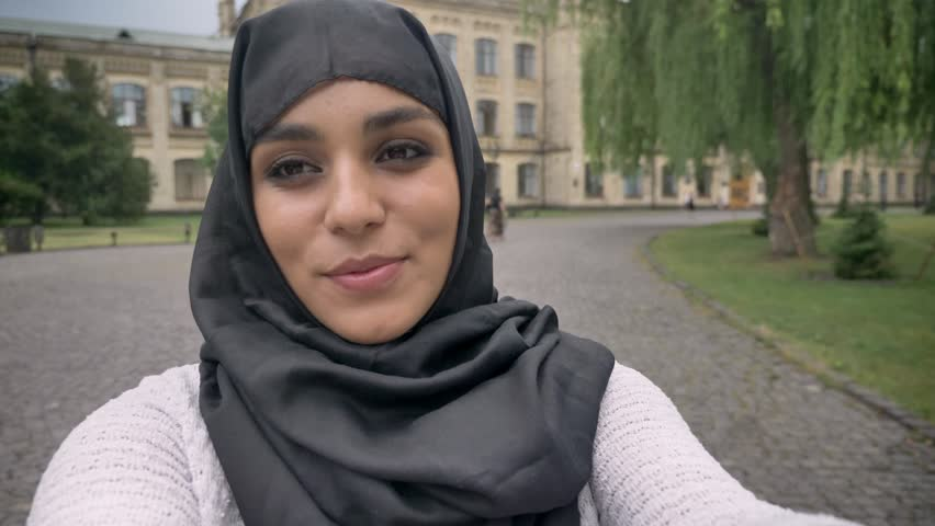 Young happy muslim girl in hijab is making video, saying hey, waving hand in blue weather, communication concept, religious concept, building on background