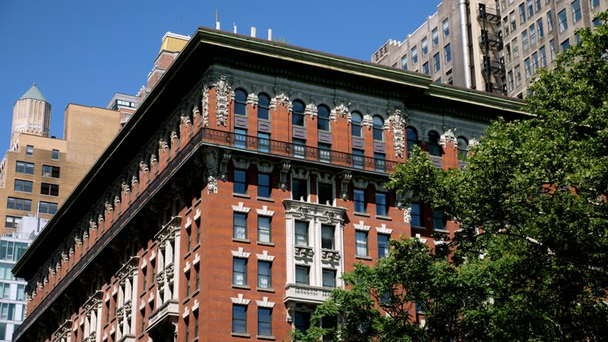 A daytime exterior establishing shot of the top of a typical red brick apartment or office building on a sunny summer day. Day/Night matching available. Shot in 5K.  | Shutterstock HD Video #1012671602