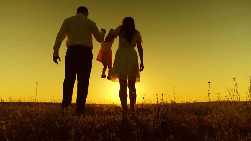 Dad and Mom hold the baby hands and walk across field at golden sunset. | Shutterstock HD Video #1012680092
