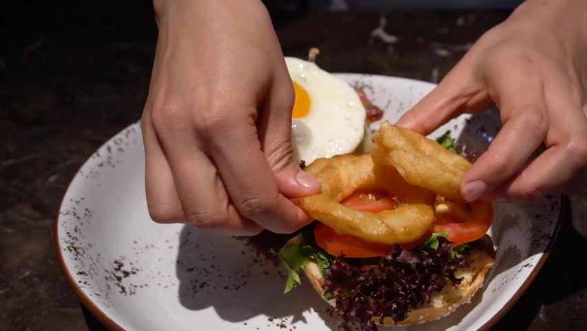 Close up view of assembling a beef hamburger lunch with fresh lettuce, bacon being placed on bread bun then topped with freshly cooked beef burger with egg, fries, fried onion rings