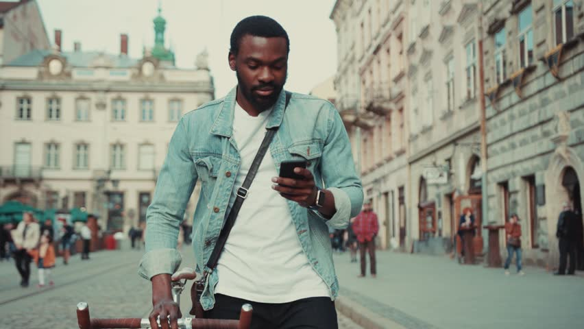 Portrait young african amerian man goes down with bike the street and uses phone look around happy smile internet face technology fashion black texting attractive smartphone handsome message