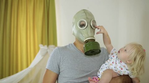 child and the man in a gas mask with disgust holding a diaper.