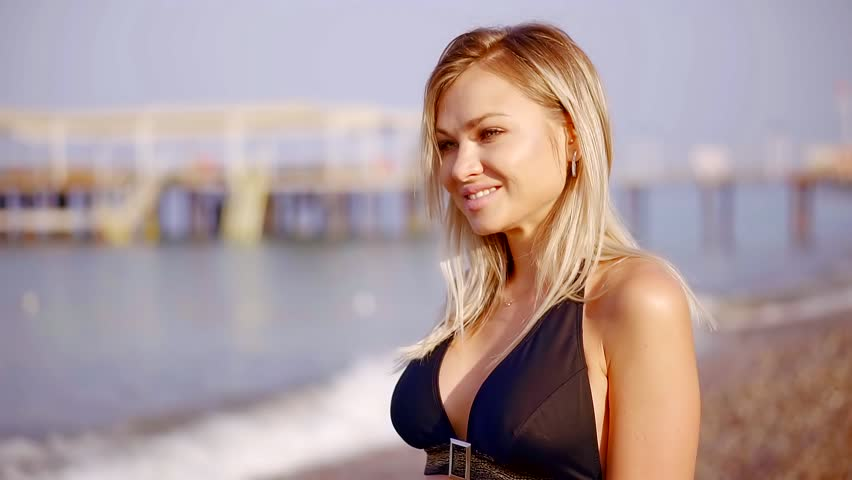 Tempting blonde woman is wearing top of black bikini standing in background of sea in summer day, touching hair | Shutterstock HD Video #1012743362