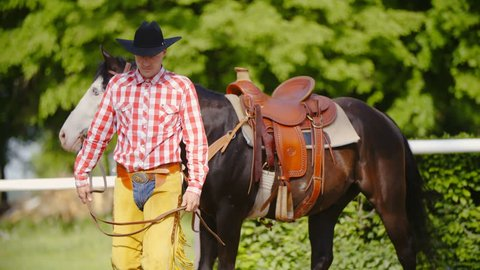 Cowboy with horse walking towards the camera in slow motion 4K. Long shot  of elegant 37bf9d922654