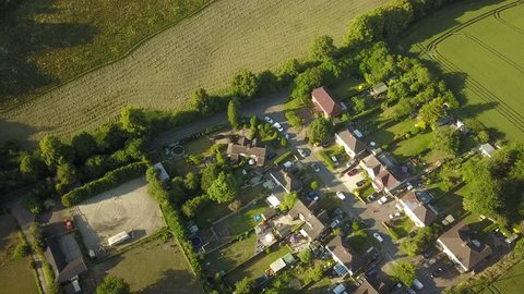 Aerial drone flight over a small farming community in rural England on a bright sunny day.  Fields and trees are bright green in the summer light.