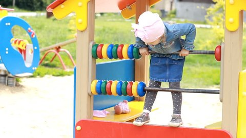Child girl plays in the playground in different games. Entertainment for children.