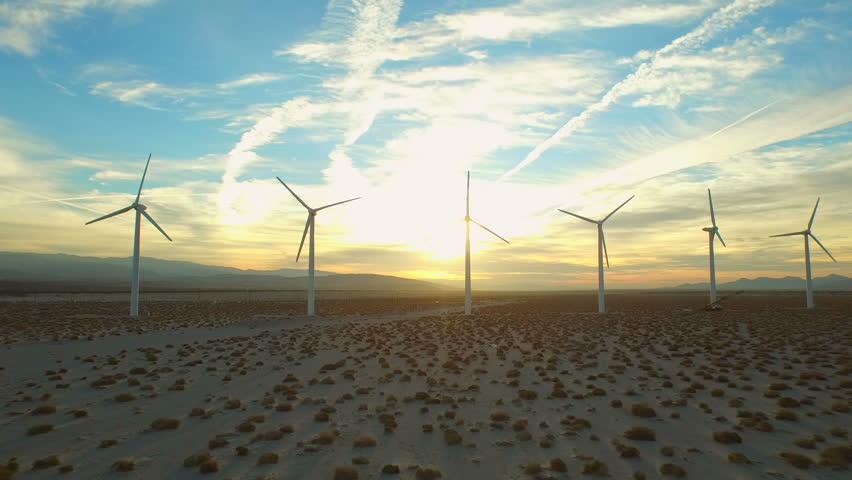 Wind Turbine Aerial v8 Flying low below large wind turbines at sunrise.