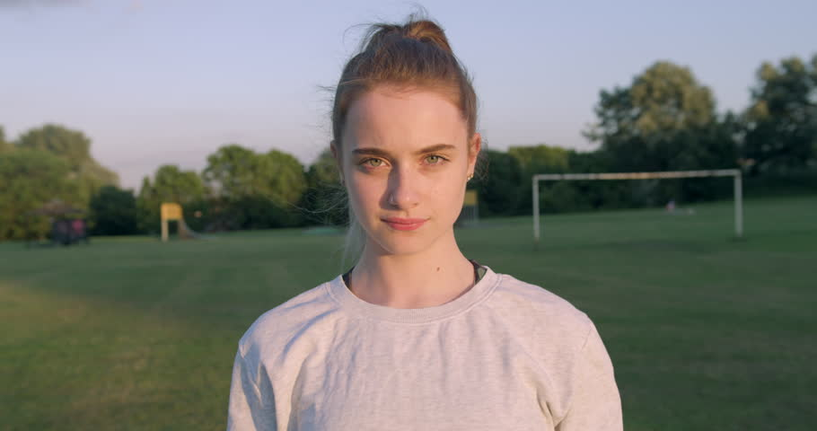 Young Woman holding a Football to her Face in a Sports Field. Smiling Blonde Girl with Foot Ball on a British Grass Soccer Park in the Sunshine. World Cup Game Celebration   Shutterstock HD Video #1012843892