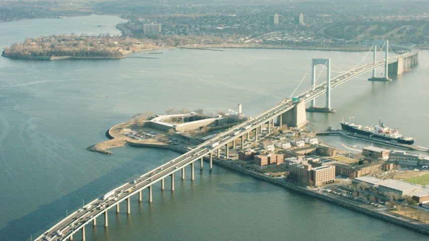 Aerial pan of cars driving along highway. Shot of highway leading to Throgs Neck Bridge in New York City. Shot with a RED camera. 4K footage.