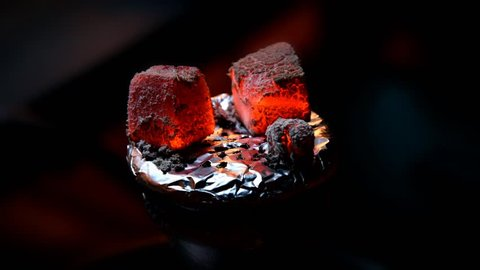 Coconut coals for a hookah pipe slowly wither away on top of a bowl of sheesha. Time-lapsed video