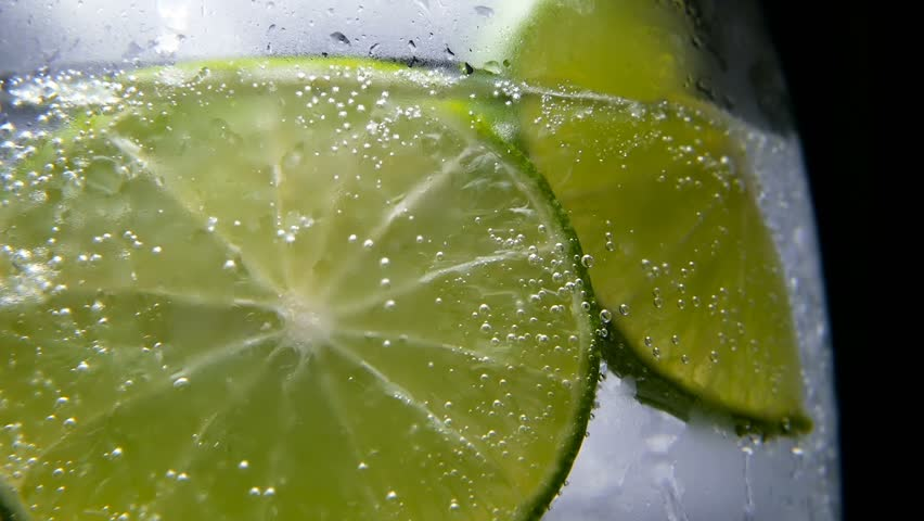 Macro close-up,refreshing soda tonic fizzy water, lime in Glass, ice. Slice of lemon, mineral bubbles. Detox or thirst concept. Healthy, dietary nutrition. Cold lemonade mojito drink. Black background