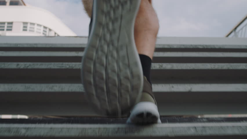 Young man athlete feet running up stairs training intense cardio workout exercise male runner legs jogging on steps in urban city background slow motion | Shutterstock HD Video #1012929152