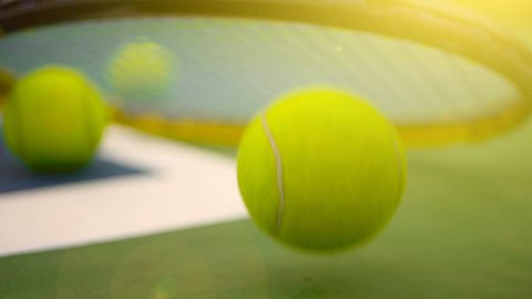 Close up of tennis equipment on the court. Sport, recreation concept. Yellow racket with a tennis ball in motion on a clay green blue court next to the white line with copy space and soft focus.