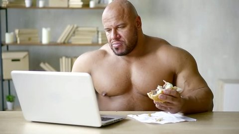 bald male bodybuilder writes text on a laptop and does not violate the diet eats a triple Burger with beef Patty