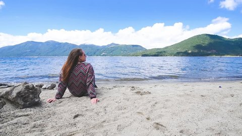Young woman relaxing in the sand at the border of a beautiful lake