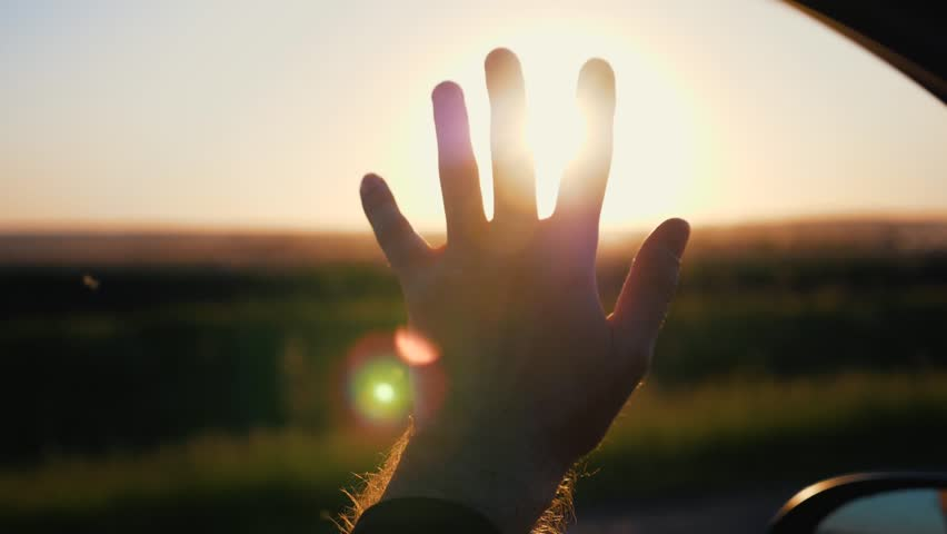 Hand of a man at sunset. Man's hand from the car window in the sun, slow motion