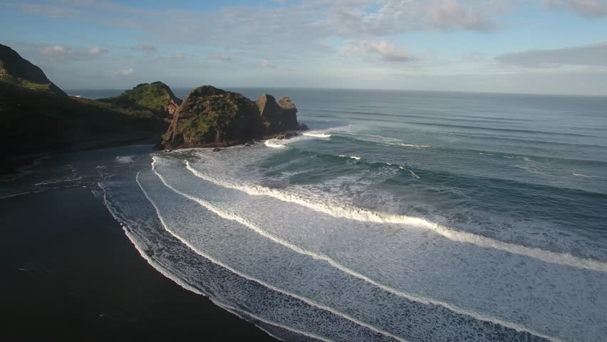 Aerial view large surfing waves at Piha Beach, New Zealand