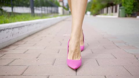 Close up shot of woman's feet in a stylish pink low heels walking on the street.